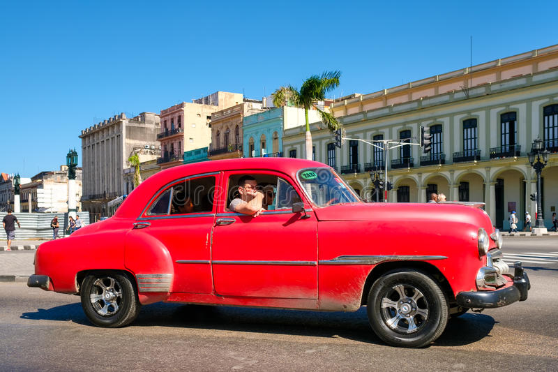 Classic red Chevrolet in downtown Havana. HAVANA,CUBA - JANUARY 24,2017 : A classic red Chevrolet in downtown Havana on a street sidelined by colorful buildings stock photography