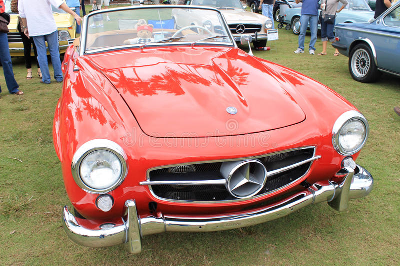 Classic red merc sports car. Front view of classic Mercedes benz 190 sl convertible sports car. full view of grille, headlamps, hood and windshield. at car show royalty free stock photo