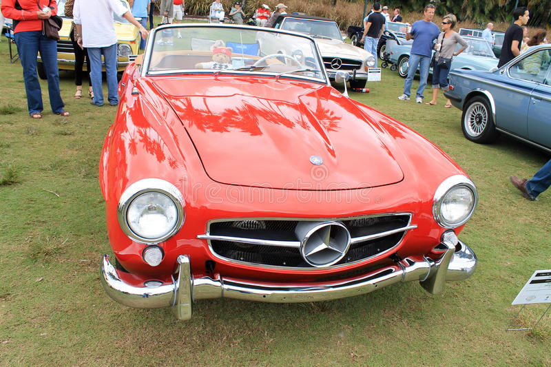 Classic red merc sports car. Front view of classic Mercedes benz 190 sl convertible sports car. full view of grille, headlamps, hood and windshield. at car show stock photo