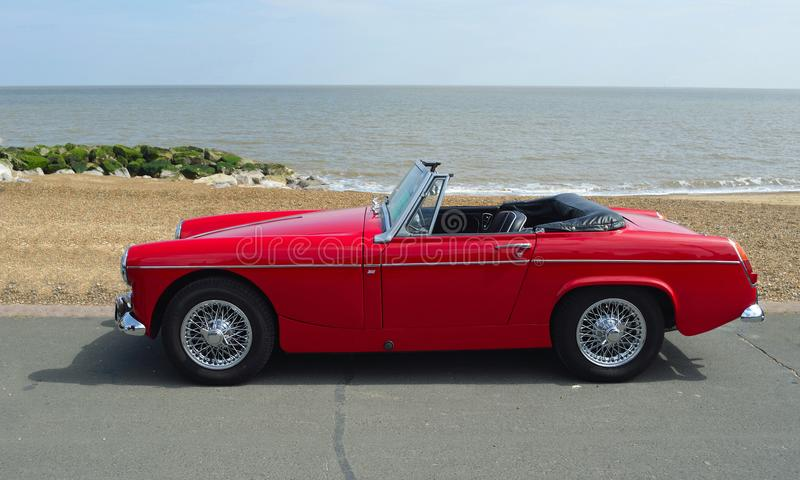 Classic Red MG Roadster Car parked on seafront promenade with sea in background. FELIXSTOWE, SUFFOLK, ENGLAND - MAY 07, 2017: Classic Red MG Roadster Car parked stock photography