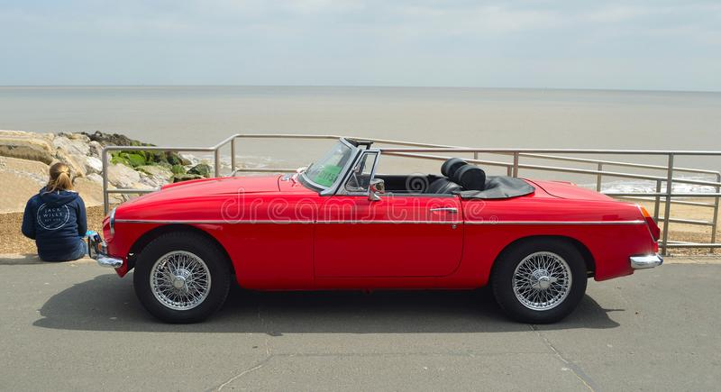 Classic Red MG Roadster Car parked on seafront promenade with sea in background. FELIXSTOWE, SUFFOLK, ENGLAND - MAY 07, 2017: Classic Red MG Roadster Car parked royalty free stock images