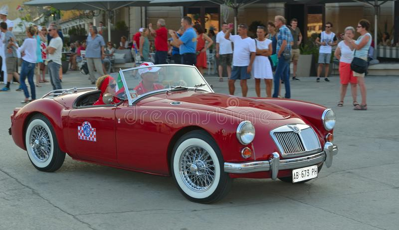 Classic Red MGA being driven through town square in Rovinj in tour of Croatia. stock images