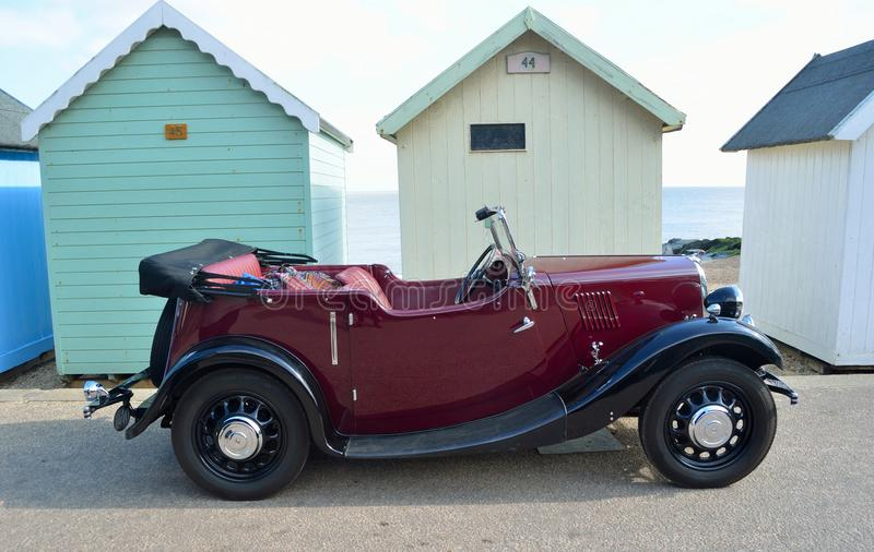 Classic Red Motor Car Parked on Seafront Promenade parked in front of beach huts. stock images