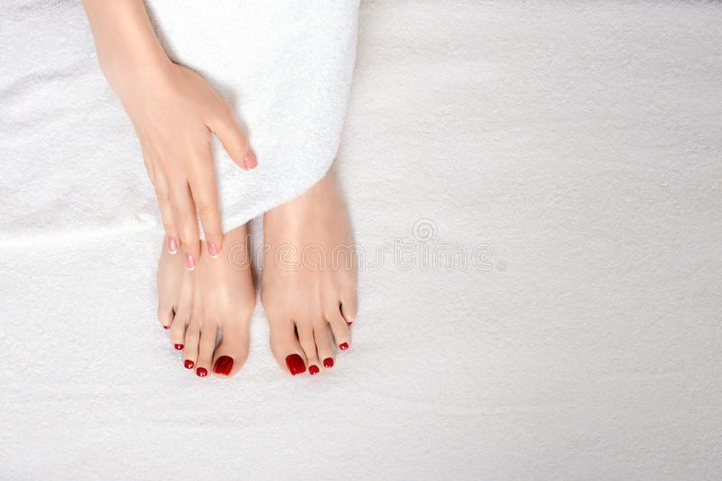 Classic red pedicure treatment. Female feet and hand on white terry towel, natural skin tone. Woman in beauty salon. stock image