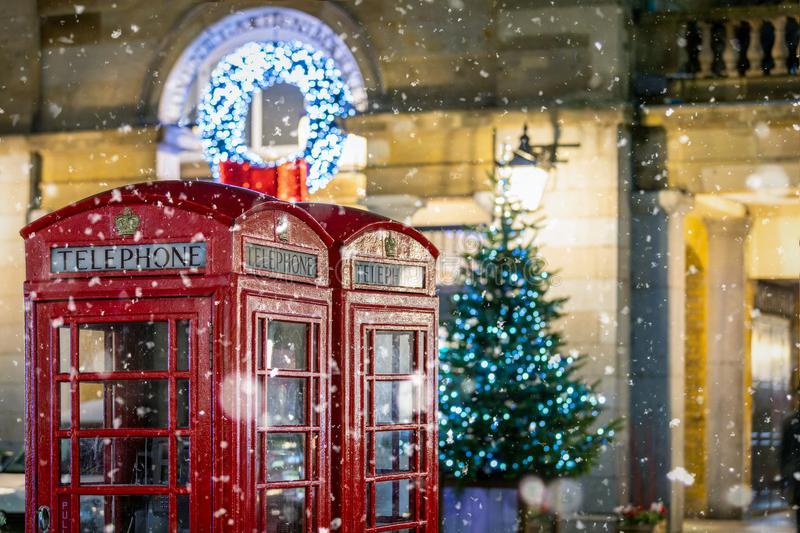 Red telephone booths in front of Christmas decorations lights in London, United Kingdom. Classic, red telephone booths with snow falling in front of Christmas stock photos