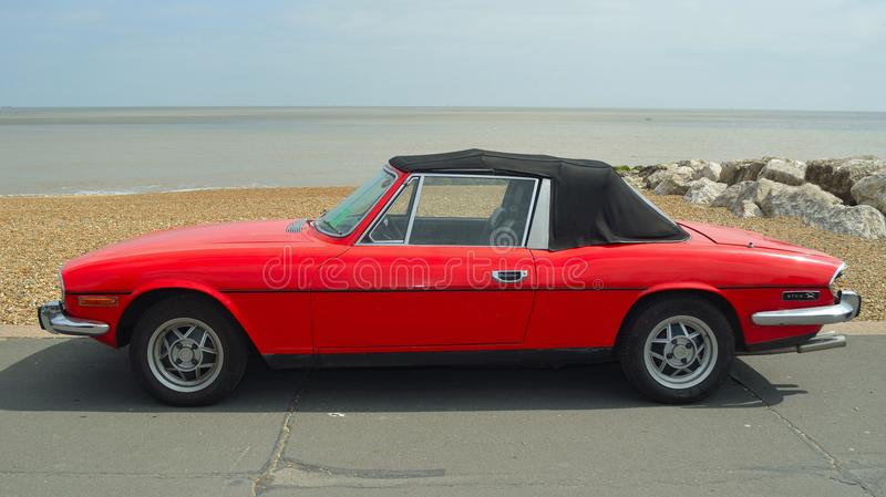 Classic Red Triumph Stag Motor Car Parked on Seafront Promenade. stock photography