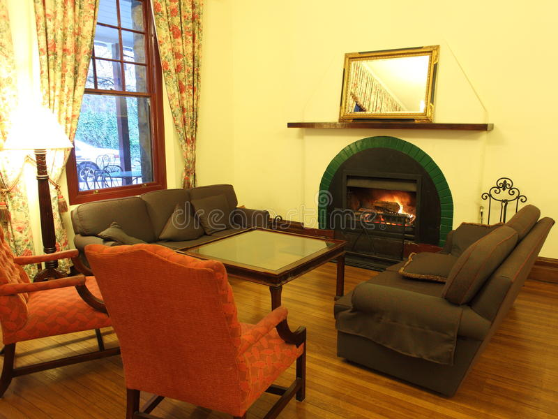Hotel lounge at fireplace. Cosy corner in a classy lounge room with open fire: retained Victorian ambiance (at Jenolan Caves, Australia) stock images