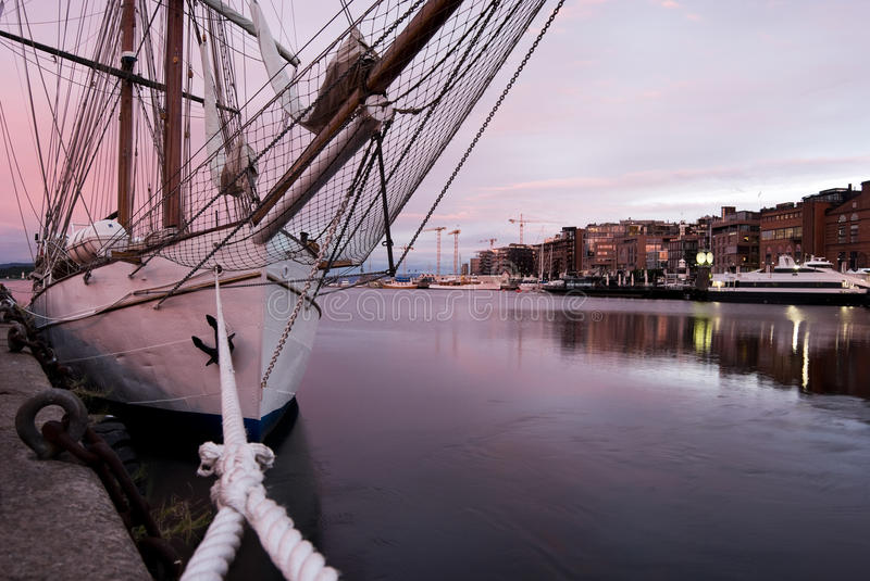 Classic sailing yacht moored in Oslo harbor. Natural pink light of the sunrise cover Oslo harbor royalty free stock images