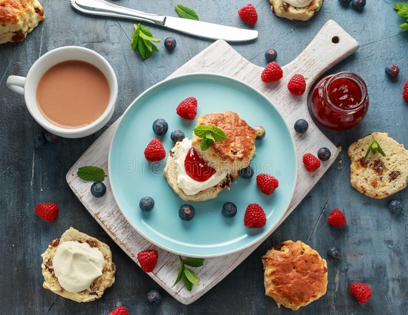 Classic scones with clotted cream, strawberries jam, english Tea and other fruit royalty free stock photo
