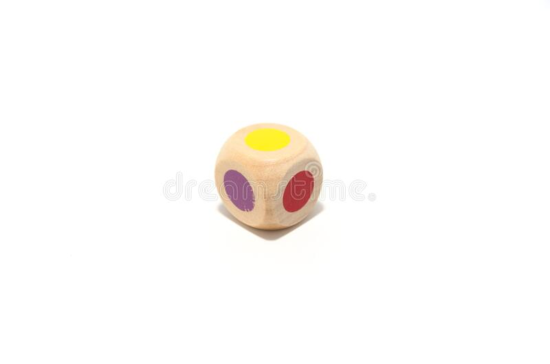 Classic six-sided wooden die with rounded edges with various colors, red, blue, yellow. Random luck. Isolated on white background royalty free stock photos