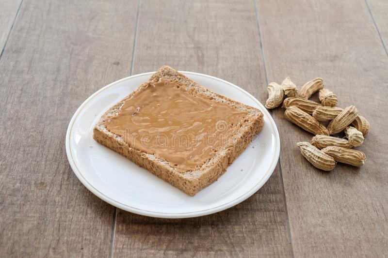 A classic slice of whole wheat bread with smooth peanut butter stock image