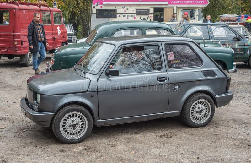 Classic small dark grey Polish car Polski Fiat 126p driving. Classic dark grey Polish little car Polski Fiat 126p built on Italian licence driving with similar royalty free stock image