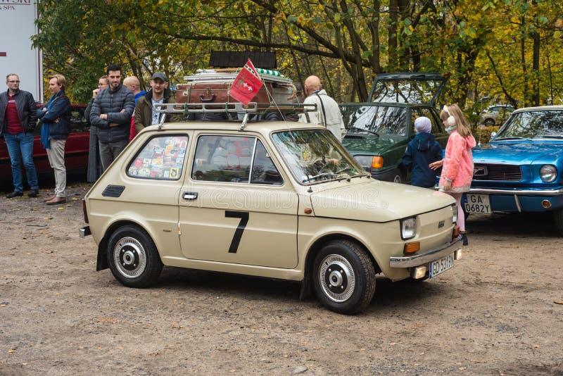 Classic small ebony Polish car Polski Fiat 126p parked. Classic ebony Polish little car Polski Fiat 126p built on Italian licence driving with similar cars at a royalty free stock photography