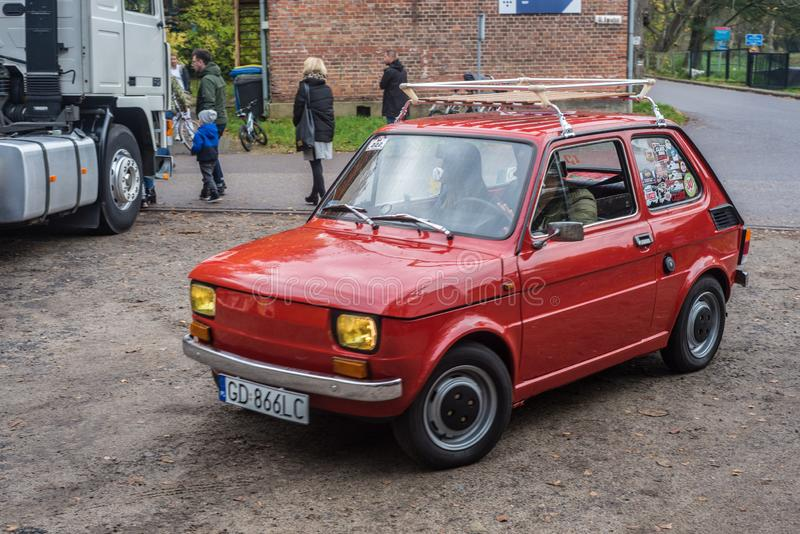 Classic small red Polish car Polski Fiat 126p driving. Classic red Polish little car Polski Fiat 126p built on Italian licence driving during car show in autumn stock image