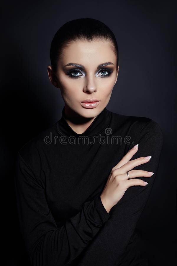 Classic Smokey makeup on woman face, beautiful big eyes. Fashion Perfect makeup, expressive eyes on girl face, smooth black stock image