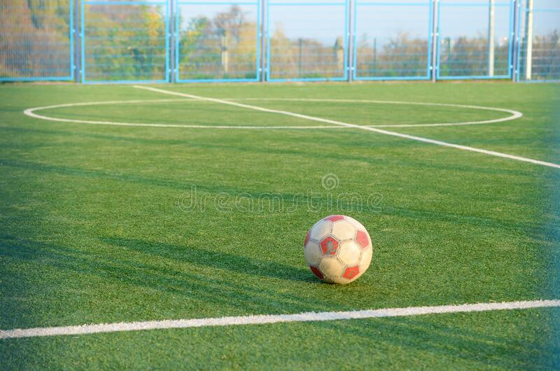 Classic soccer ball on football green grass field outdoor. Active sports and physical training royalty free stock photography