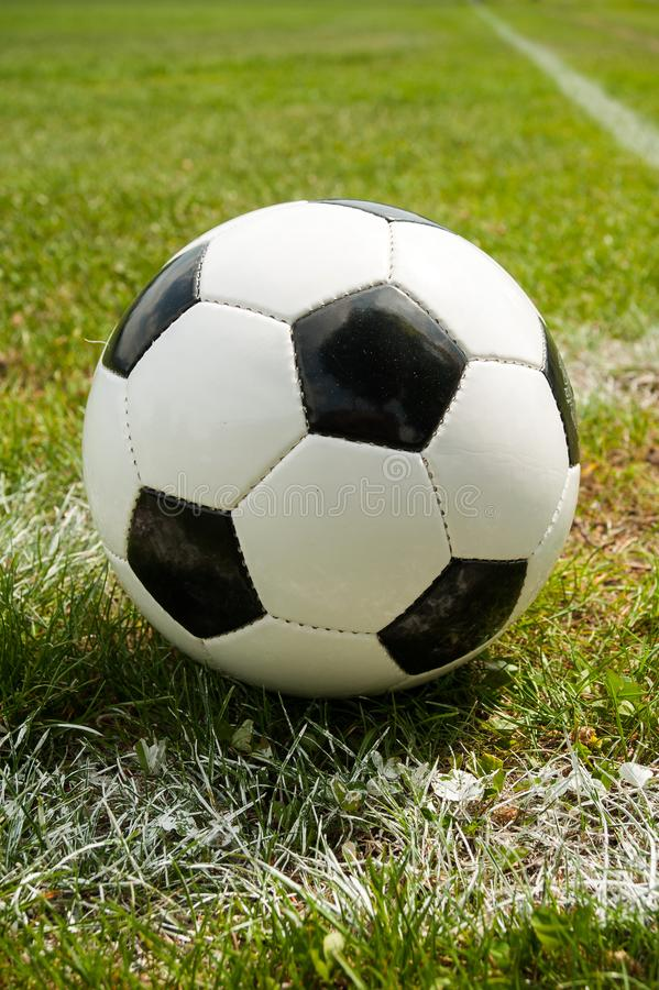 Classic soccer ball lying at the corner in the grass, it is a sunny day in summer royalty free stock image