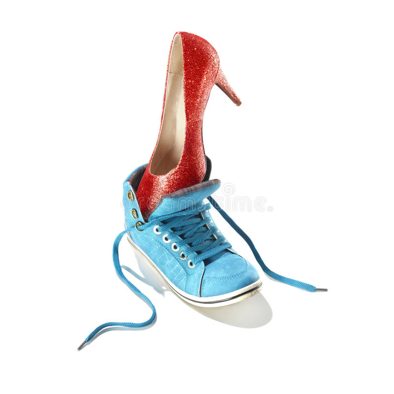 Classic stiletto high heels shoe put in a sport shoe. Classic stiletto high heels shoe in a red snake-print design put in a blue sport shoe royalty free stock photos
