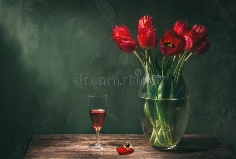 Classic still life with beautiful red tulip flowers bouquet in transparent glass vase and a glass of red wine. Art photography.  stock image