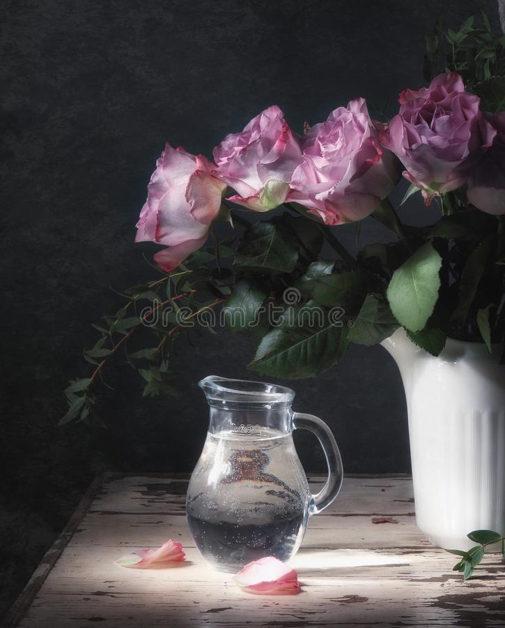 Classic still life with a bouquet of pink roses and a jug with pure tasty clear water. Art photography. royalty free stock photography
