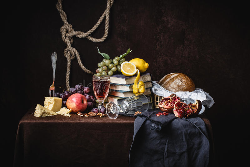 A classic still-life in the Dutch style. With fruit cheese and books. On a dark brown background. With draperies stock images
