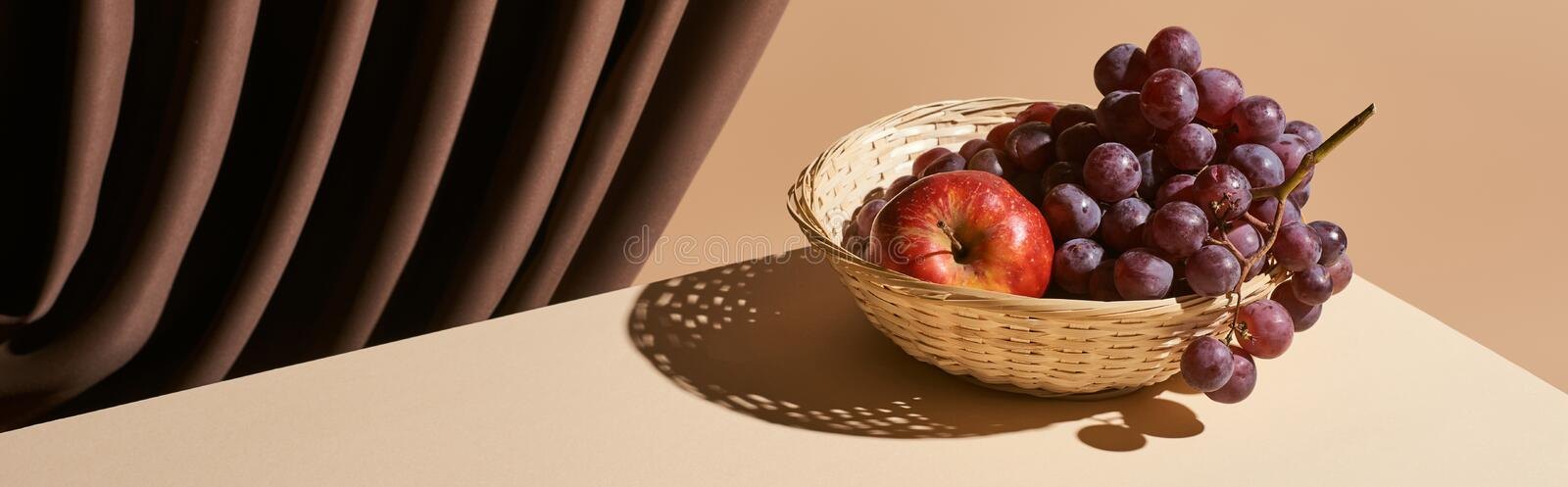Classic still life with pomegranate and grape in wicker basket on table near curtain isolated on beige, panoramic shot. Stock photo royalty free stock photography