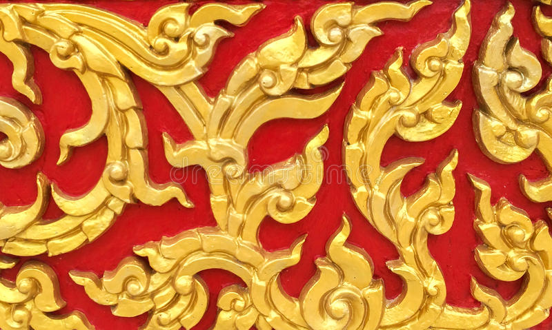 Classic Stone Carvings Thai Vintage Style Art of Golden Floral Seamless Pattern on Red Concrete Background Texture used as Beautif. Classic Stone Carvings in stock photos