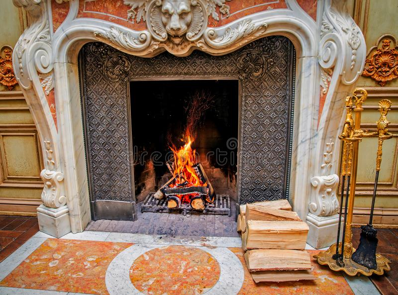 A classic style fireplace with burning firewood. royalty free stock photo