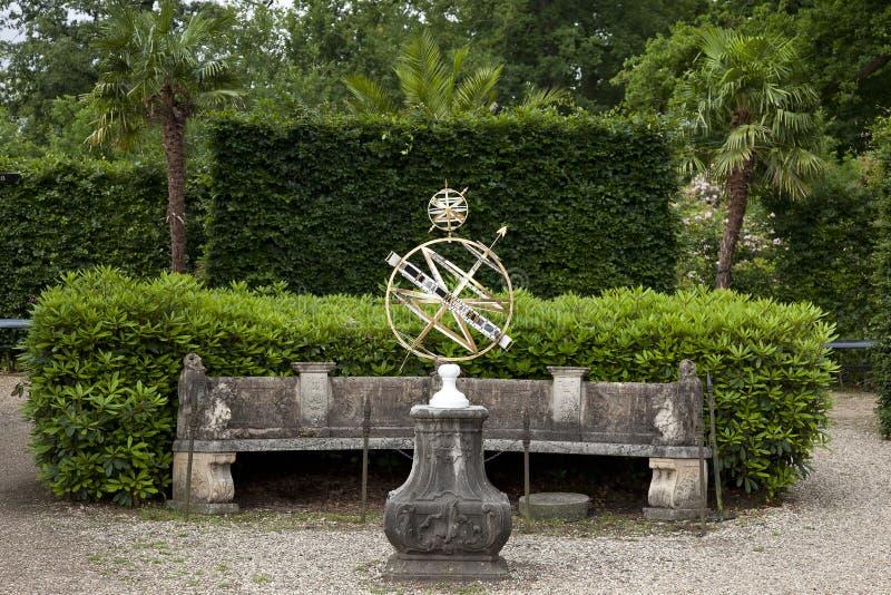 Classic sundial on stone plinth in beautiful formal garden of Twickel Estate, Hof van Twente. Beautiful forged sundial on ornate old stone plinth in the formal stock photo
