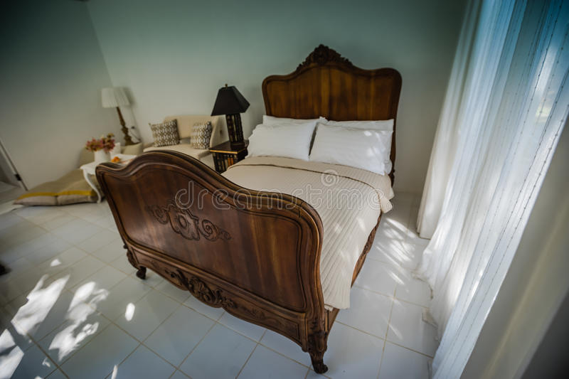 Classic teak wood bed furniture in the warm and cozy bedroom, ne. Xt to the windows with morning sunlight stock images