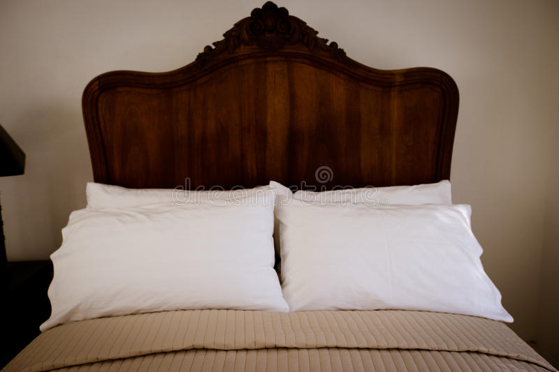 Classic teak wood bed furniture in the warm and cozy bedroom, ne. Xt to the windows with morning sunlight stock photos