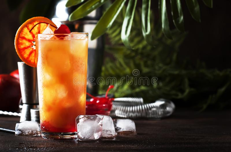 Classic tequila sunrise cocktail with silver tequila, grenadine syrup, orange and ice cubes. Wooden bar counter in the bar. Summer. Mood concept. Selective royalty free stock photography
