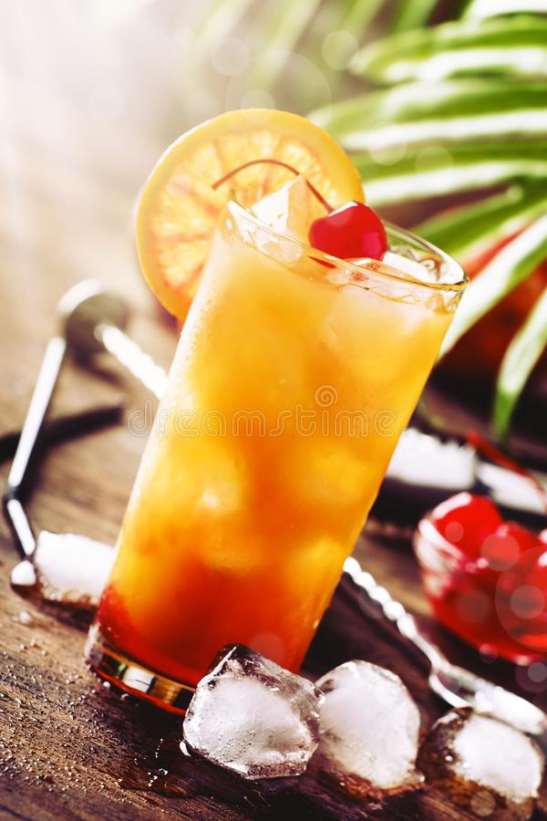Classic tequila sunrise cocktail with silver tequila, grenadine syrup, orange and ice cubes. Wooden bar counter in the bar. Summer. Mood concept. Selective stock photography