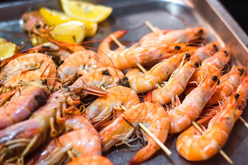 Classic tiger shrimp skewers. Shrimps sriracha kebabs with lemon for dinner. Delicious prawn spit prepared on grill. Extreme close. Up of appetizing grilled stock image