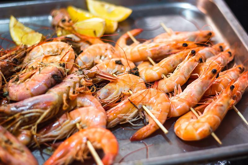 Classic tiger shrimp skewers. Shrimps sriracha kebabs with lemon for dinner. Delicious prawn spit prepared on grill. Extreme close. Up of appetizing grilled royalty free stock image