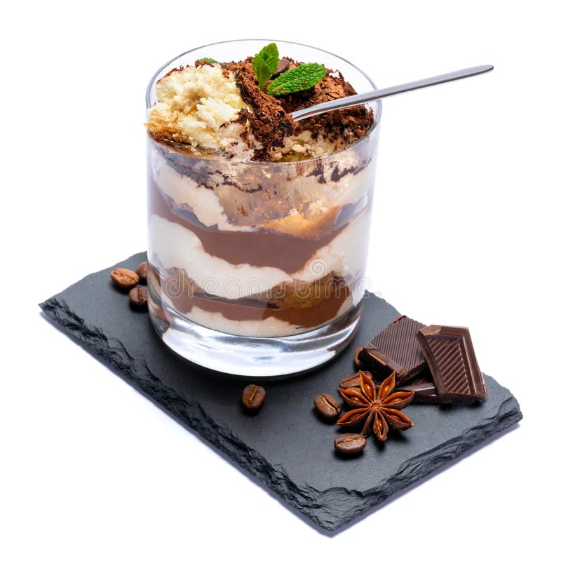 Classic tiramisu dessert in a glass cup and pieces of chocolate on stone cutting board on white background with clipping. Path embedded stock images
