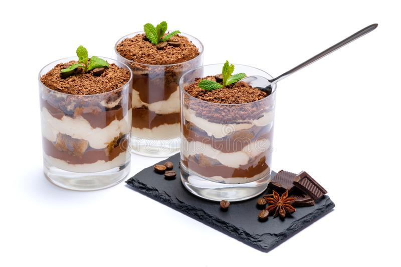 Classic tiramisu dessert in a glass cup on stone serving board and pieces of chocolate on white background with clipping. Path embedded stock images