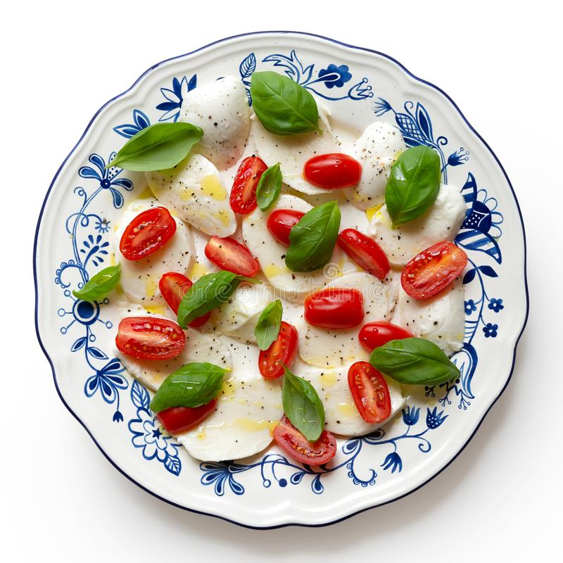 Classic tomato, fresh basil and mozzarella salad. On blue and white ornate plate drizzled with olive oil and black pepper isolate stock photography