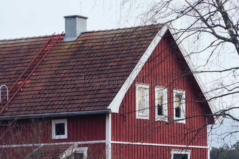 Classic traditional red wooden house in Scandinavia countryside, roof closeup. stock photography