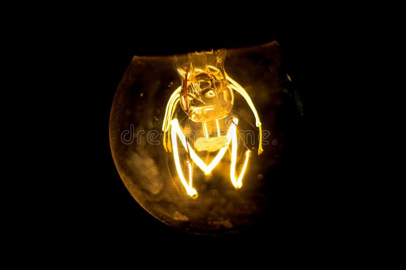 Classic tungsten filament lamp glowing bright in black background. Classic tungsten filament lamp, side view, orange, easy to edit. wesak bulb, glass bulb, with royalty free stock photography