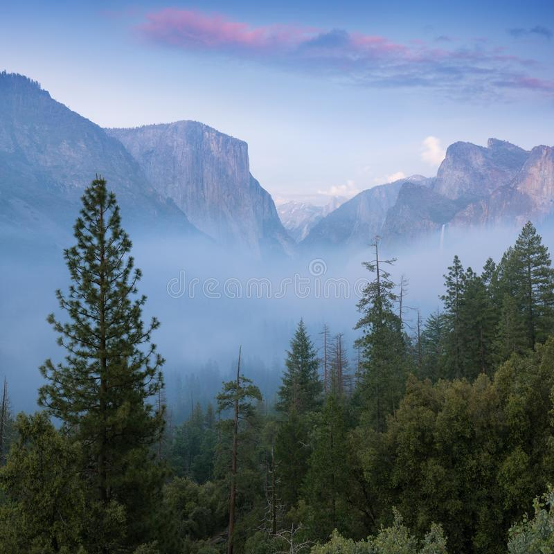 Classic Tunnel View of scenic Yosemite Valley with famous El Capitan and Half Dome rock climbing summits in beautiful royalty free stock photo