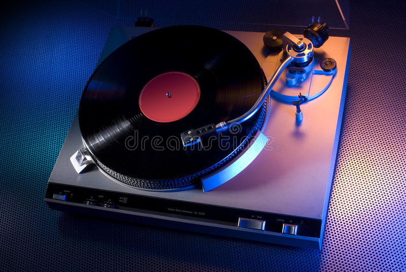 Classic turntable. Silver classic vinyl record turntable on hi-tech steel table lit with orange and blue lights royalty free stock photography