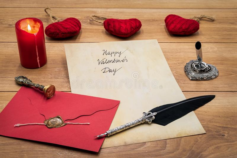 Classic Valentine`s Day cad with decorative quill and stand, red envelop with wax seal, red candle and cuddle, space for your text stock images