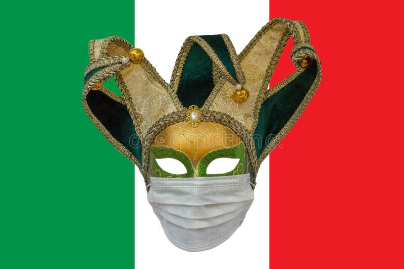 Classic venetian carnival mask in a medical protective mask against the background of the flag of Italy. The concept of the spread. Of coronavirus in Italy stock photos