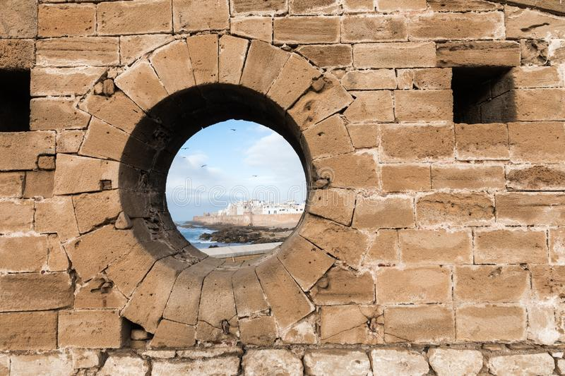 Classic view of medina Essaouira through a hole in the wall of t. He fortress, Morocco. UNESCO world heritage site stock photo