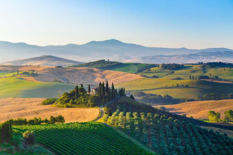 Scenic Tuscany landscape at sunrise, Val d`Orcia, Italy. Classic view of scenic Tuscany landscape with famous farmhouse amidst idyllic rolling hills and valleys stock photo