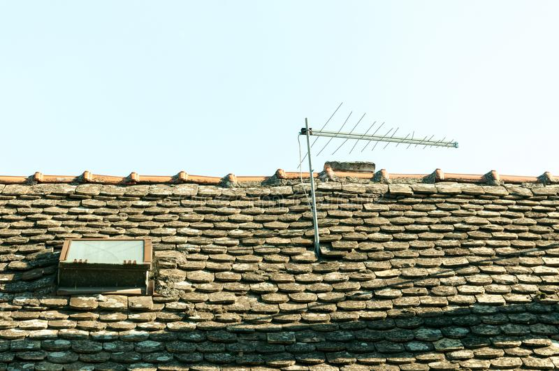 Classic vintage analog television antenna on the old house roof with tiles and window. stock images