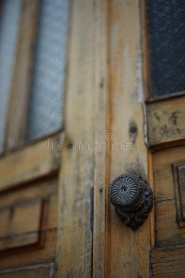 Classic black door knobs with carvings on old brown wooden doors stock photo