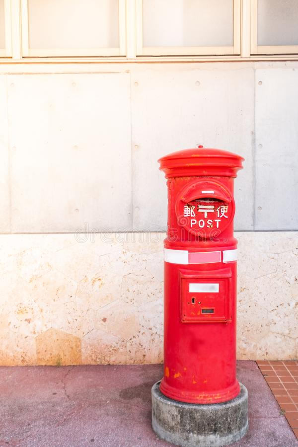 Classic vintage Japanese style postbox with cement wall background. Red English pillar box royalty free stock photos