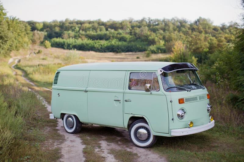 Classic vintage mint color camper van parked in the field. On trail road royalty free stock photos